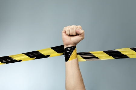 cordon: Hand tangled in black and yellow barrier tape. Stock Photo