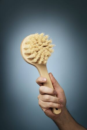 bristle: Man holding a brush made of wood and natural fibers in his hand.