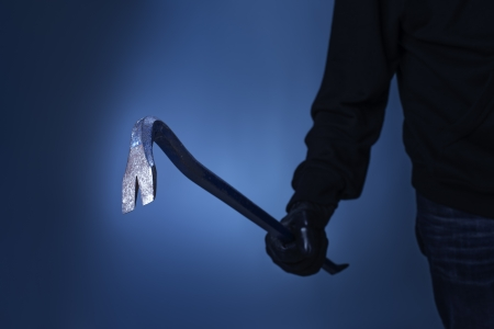 pry: Burglar holding a crowbar in his hand. Stock Photo