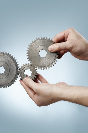 Man designing a mechanic system with old metallic cog gear wheels. Stock Photo - 16024983