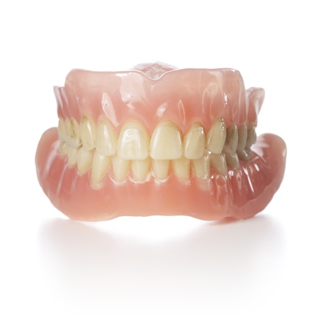 Old dentures with yellowed teeth isolated on white with reflection.