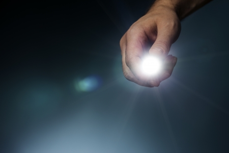 illuminate: Man pointing a led flashlight towards camera.