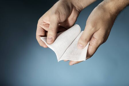 unfolding: Hands holding a sterile medical textile gauze bandage. Stock Photo