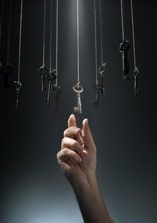 Hand choosing a hanging key amongst other ones.