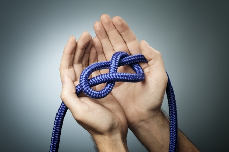 knotting: Man holding a blue rope with a figure of eight knot in his hands. Stock Photo