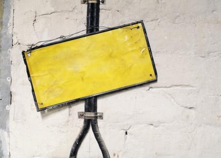 impiccata: Vecchio segno in bianco metallico impiccato di fronte a cavi elettrici.
