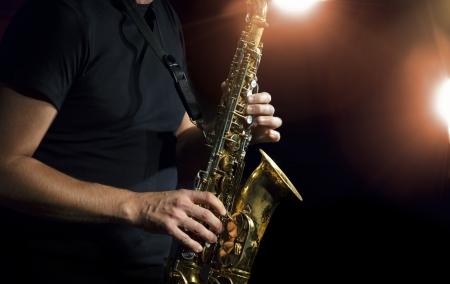 saxofón: Músico que toca el saxofón alto en un concierto. Foto de archivo
