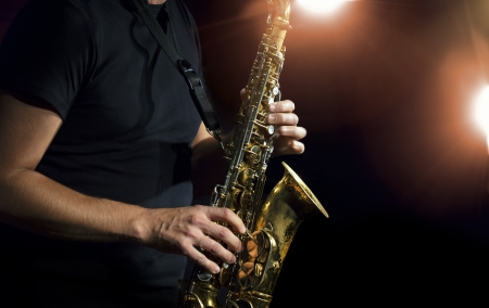 Musician playing alto saxophone on a gig. Stock Photo