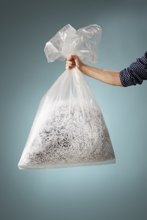 shreds: Man holding a transparent plastic bag with shredded paper. Stock Photo