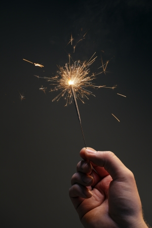 Man holding a burning sparkler firework in his hand. photo