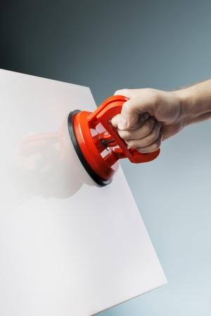 lifter: Man lifting a white ceramic tile using a vacuum suction cup tool aka dent puller.