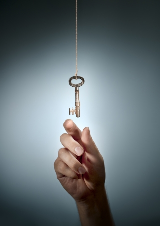 old key: Conceptual image of a hand taking an old key hanging from a string. Stock Photo