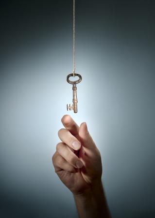 � image: Imagen conceptual de una mano tomando una vieja llave que cuelga de una cadena.