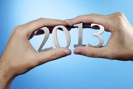 Happy New Year 2013. Man holding metallic numbers 2013 in his hands. Stock Photo - 16438850