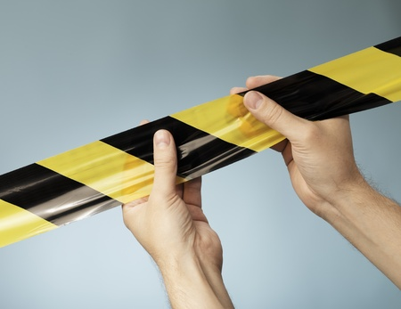 restrictions: Man holding black and yellow striped barrier tape in his hands. Stock Photo