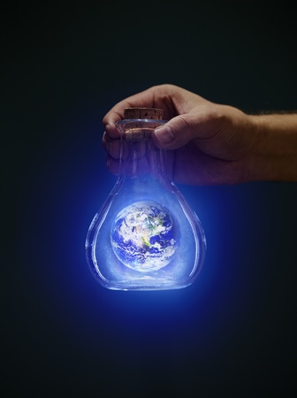 hand holding globe: Man holding an old bottle with a glowing earth. Earth image provided by NASA.