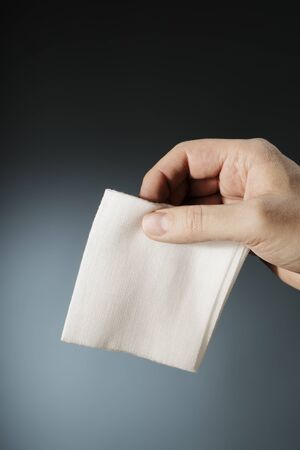 gauze: Man holding a folded sterile medical gauze in his hand.