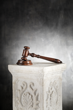 High quality mahogany gavel with sound block on a plaster column. photo