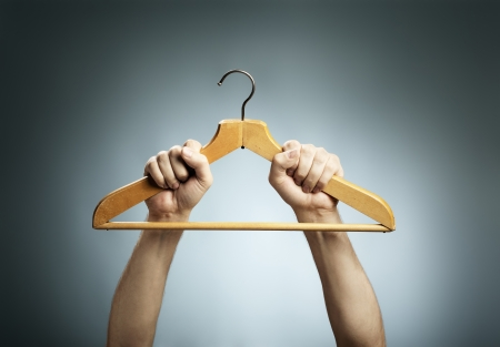 coathanger: Man holding an old wooden clothes hanger in his hands.