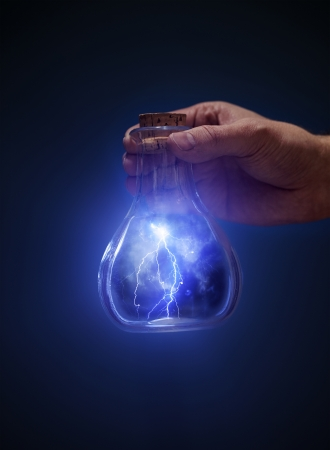 Man holding an old bottle with lightnings in his hand. Stock Photo