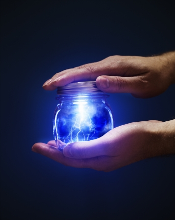 Conceptual image of a man holding a jar with lightnings in his hands.
