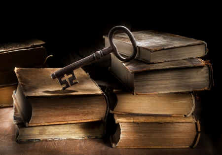 Conceptual still life image of old antique books and a big old key. photo
