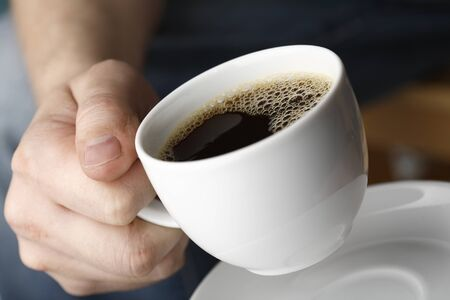 bodypart: Hand with a cup of fresh black coffee.