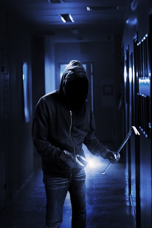 Burglar with flashlight and crow bar in a dark office building. Stock Photo
