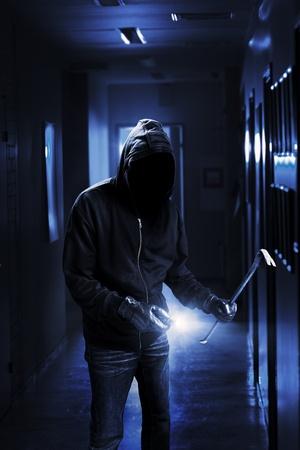 Burglar with flashlight and crow bar in a dark office building. Standard-Bild