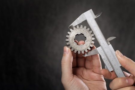 caliper: Man measuring the diameter of old cog with vernier caliper. Lots of copy space to the left.