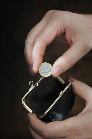Man with coin purse showing his last 1 euro coin. Very short depth-of-field. Stock Photo - 18724946