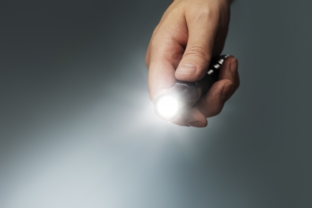 Man holding a small but powerful led flashlight in his hand. photo