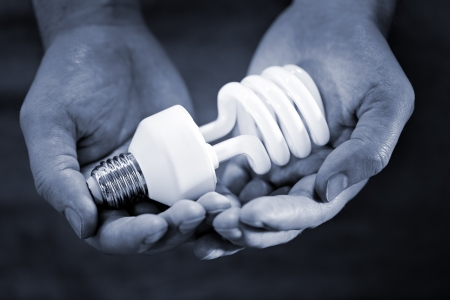 e27: Blue toned monochrome image of hands holding a compact fluorescent bulb. Very short depth-of-field. Stock Photo
