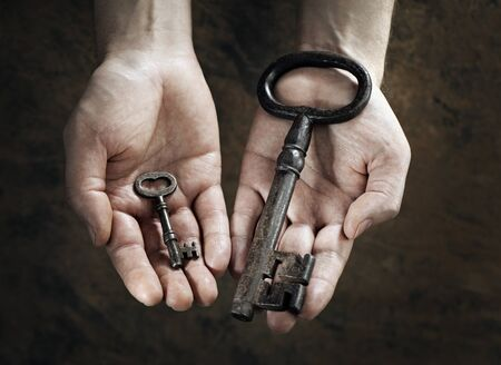 contrasting: Man holding a big and a small key in his hands. Stock Photo