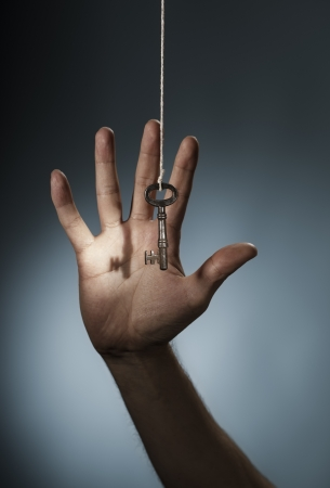 A Key hanging from a string in front of a hand. photo