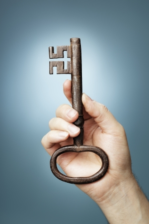 Man holding a big antique skeleton key in his hand. Stock Photo - 18724951