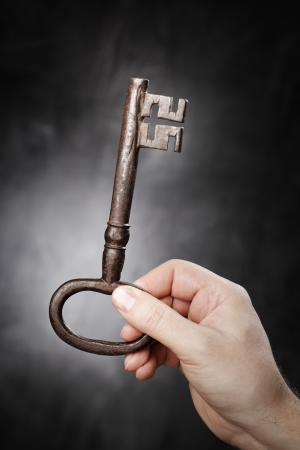 Man holding big old antique key in his hand. Stock Photo - 18724950