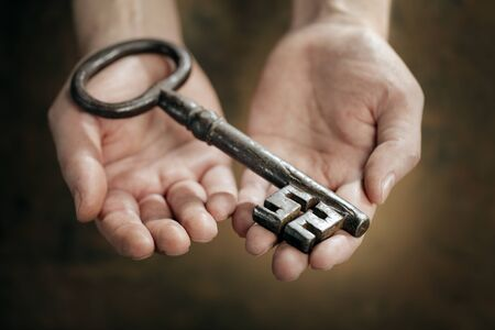 Man holding a big old antique skeleton key in his hands. Very short depth-of-field. Stock Photo - 18724958