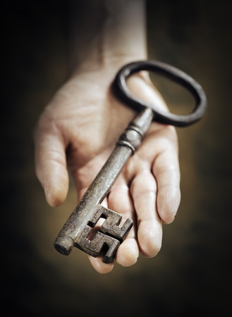 Man holding big antique key in his hand. Very short depth-of-field. Stock Photo - 18724941