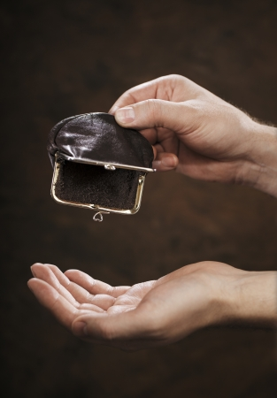 coin purse: Man holding an empty small change coin  purse in his hand.