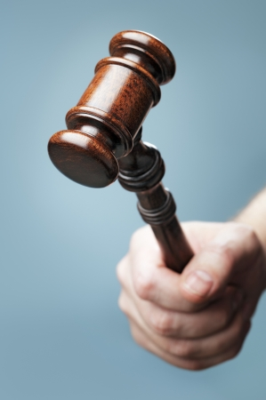 auctioneer: Man holding a wooden mahogany gavel in his hand. Short depth-of-field. Stock Photo