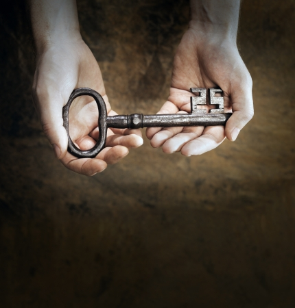 Man holding a big old antique skeleton key in his hands. Very short depth-of-field.