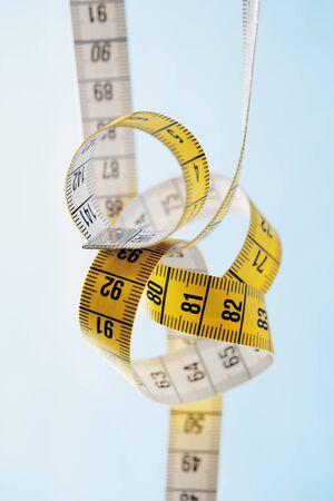 metric: Tangled yellow and white metric tape measure. Stock Photo