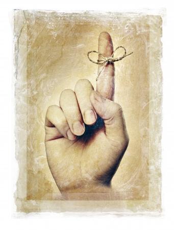recordar: Imagen de colores, granulada y arenosa de una mano con una cuerda atada alrededor del dedo índice.