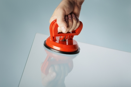 suction: Man lifting a sheet of glass using a vacuum suction cup tool aka dent puller.