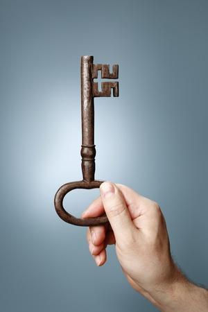 Man holding a big old key in his hand Stock Photo - 21240241