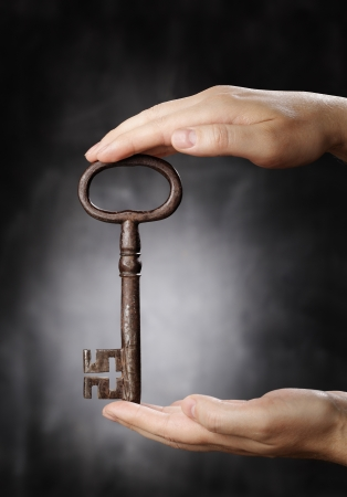 Man holding big old antique skeleton key in his hands Stock Photo - 21240244
