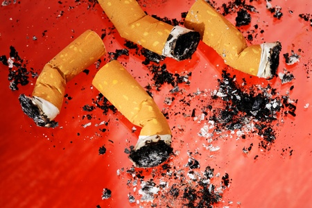 quitting: Cigarette Butts with ashes on red background.