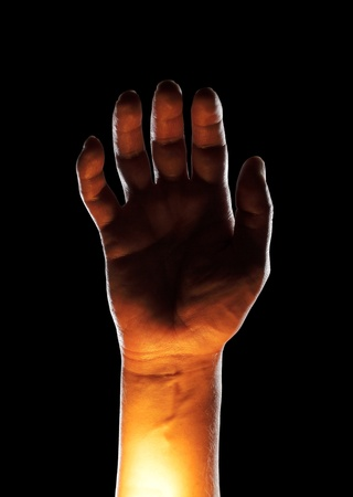 A Mans hand lit from below.
