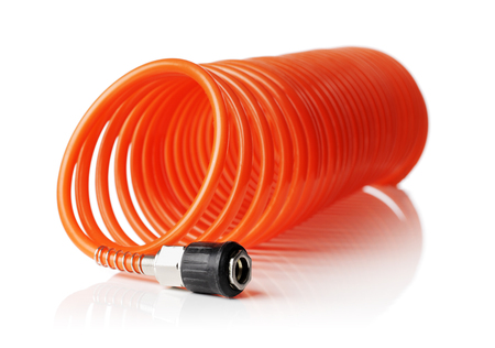 compressed air hose: Orange red thin spiral air hose used for pneumatic tools. Isolated on white with natural reflection. Very short depth-of field, the sharpness is in the connector.